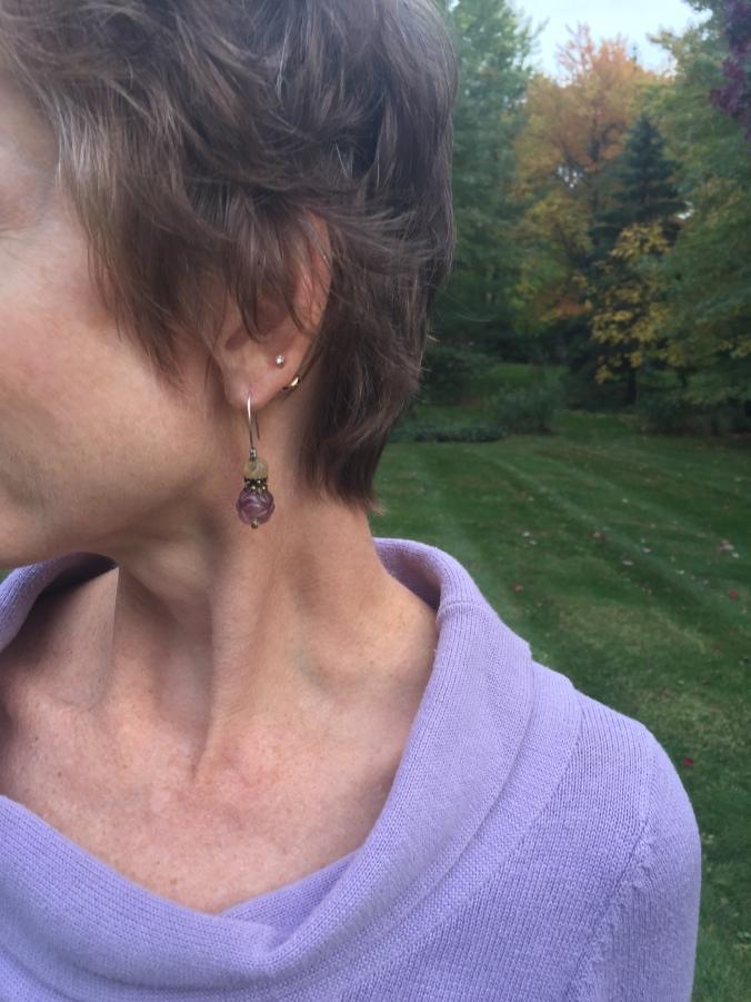 Elle wearing purple/cream earrings
